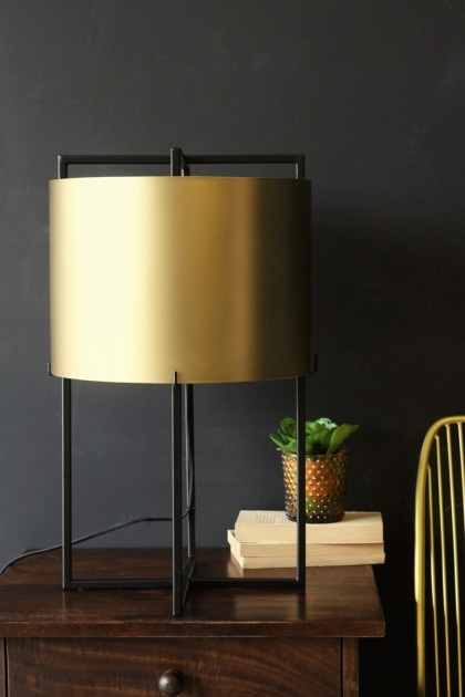 lifestyle image of Cayan Metal Table Lamp on wooden table with pile of books and plant with dark wall background