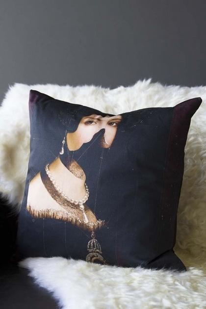 lifestyle image of Celia Cushion on white sheepskin and dark grey wall background