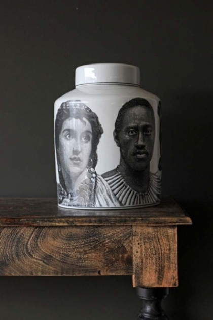 Ceramic fornasetti style faces jar with faces on it and on wooden shelf with dark wall background lifestyle image