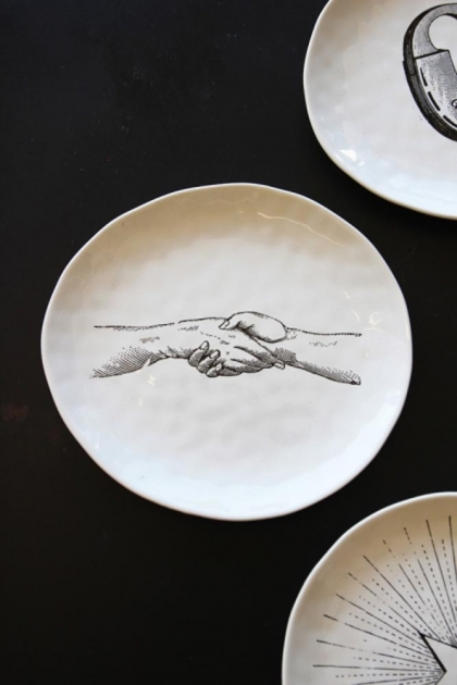 Handmade ceramic plate with a pair of holding hands drawn on it