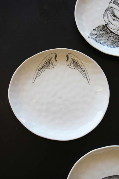 Handmade white ceramic plate with wings drawn on it