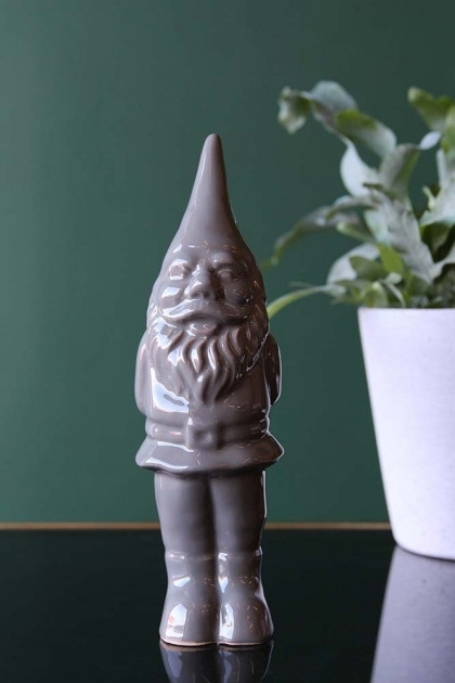 lifestyle image of Cheeky Ceramic Gnome - Grey on black table with plant and dark green wall background
