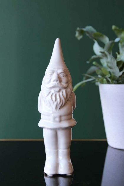 lifestyle image of Cheeky Ceramic Gnome - White on black table with plant and dark green wall background