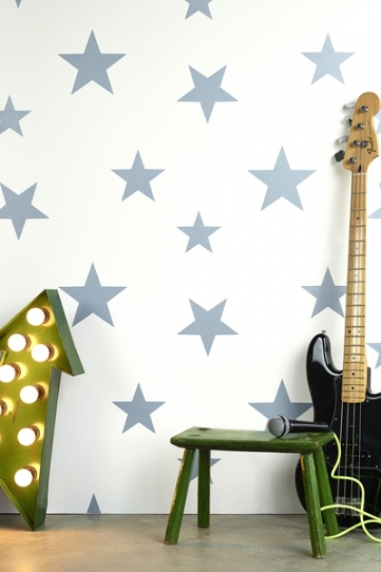 Lifestyle image of Hibou Home Wish Upon A Star Children's Wallpaper with green light up arrow. green small stool and black electric guitar