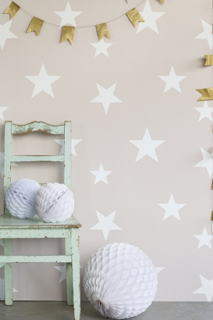 Lifestyle image of Hibou Home Wish Upon A Star Children's Wallpaper - Blush/White with distressed blue chair, white ball decorations and gold bunting