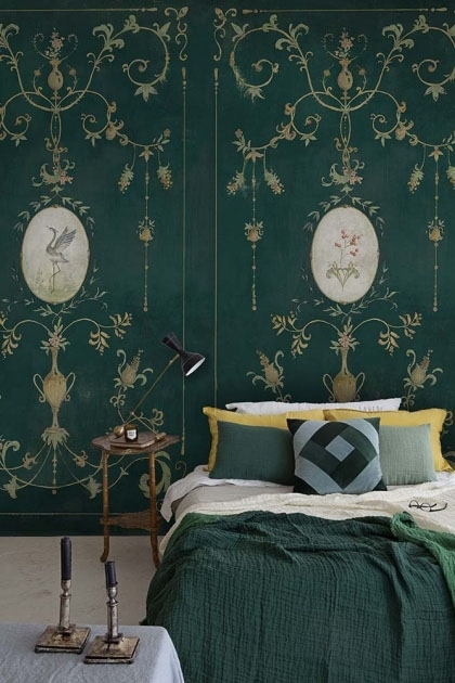 Lifestyle image of the Chinoiserie Panel Wallpaper Mural - Mirto Aloe with double bed with dark green bedding and dark wooden side table with table lamp on top and table with candlesticks on in foreground