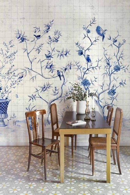 Lifestyle image of the Chinoiserie Tile Wallpaper Mural - Meihua Blue Spirulina with wooden dining table and dining chairs around it with candlesticks and white vase with plant in on patterned flooring