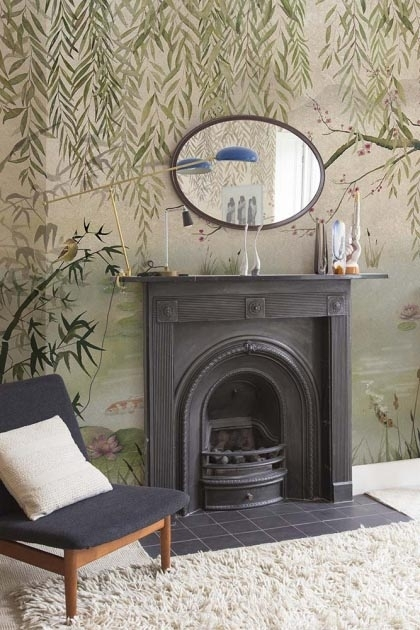 Lifestyle image of the Chinoiserie Wallpaper Mural - Lotus Aloe with black fireplace with oval mirror hanging on wall above it and dark armchair with white pillow on top