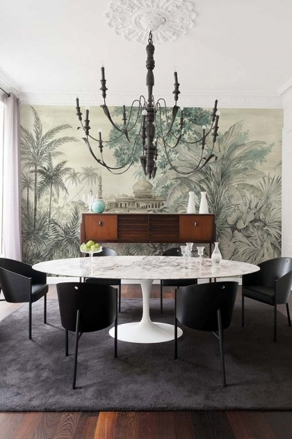 Lifestyle image of the Chinoiserie Wallpaper Mural - Taj Mahal Maca with large white round dining table and black dining chairs below black chandelier and on dark grey rug