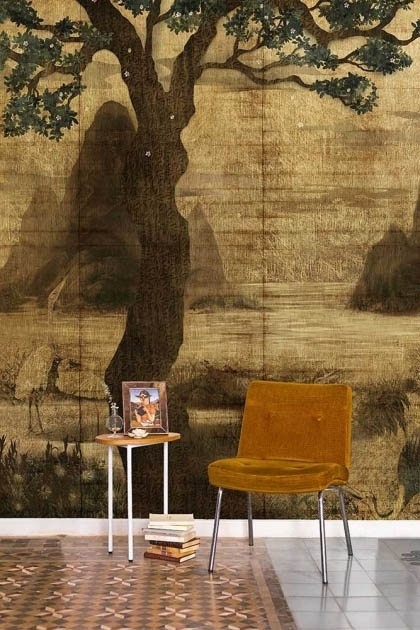 Lifestyle image of the Chinoiserie Wallpaper Mural - Zilant Chai with brown chair and side table with picture frame on and pile of books on tiled flooring