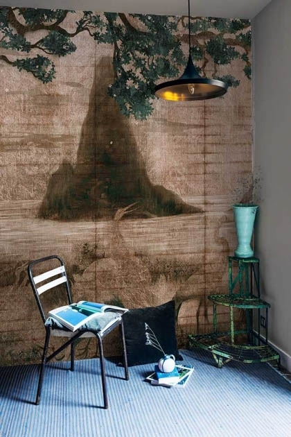 Lifestyle image of the Chinoiserie Wallpaper Mural - Zilant Rose Pink with white chair with magazine on it and green side table with blue vase on it on blue flooring