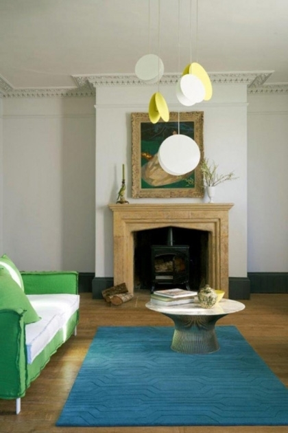lifestyle image of Circuit 100% Wool Rug - Various Colours & Sizes with fireplace, green sofa and wooden flooring with pale walls