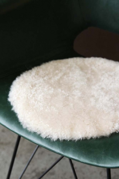 lifestyle image of Circular Sheepskin Wool Pad - Pearl Beige on green chair with concrete flooring