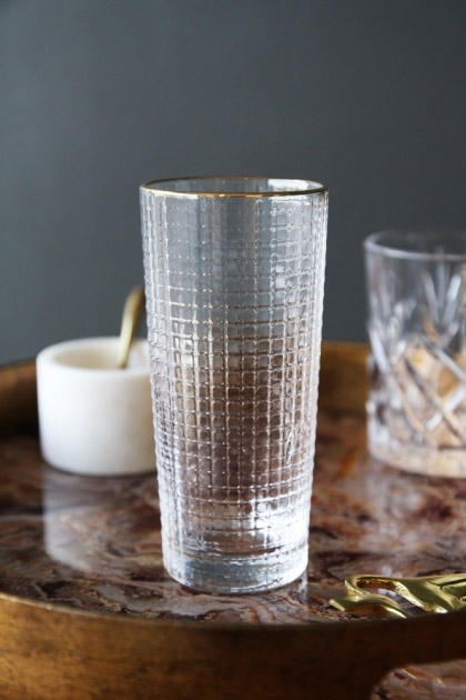 lifestyle image of Clear Glass Tumbler With Gold Rim on marble top side table with candle and other glass