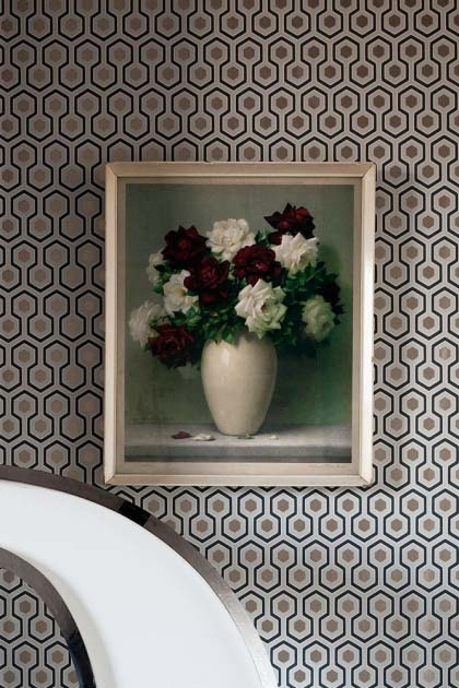 lifestyle image of Cole & Son Contemporary Restyled - Hicks' Hexagon Wallpaper - 3 Colours Available with flower picture in frame on wall and white chair in front