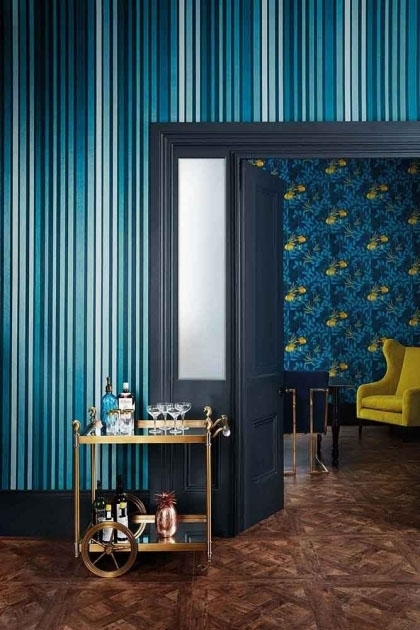 lifestyle image of Cole & Son Marquee Stripes Collection - Carousel Stripe Wallpaper - Inky Blue with large door way with yellow armchair and gold drinks trolley