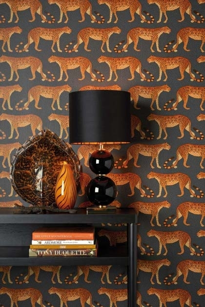 lifestyle image of Cole & Son - The Ardmore Collection - Leopard Walk with black desk in front with black table lamp and amber vases on top