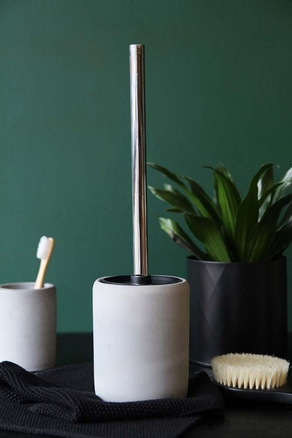 lifestyle image of Concrete Loo Brush with Concrete Toothbrush Mug and plant on black table and dark green wall background