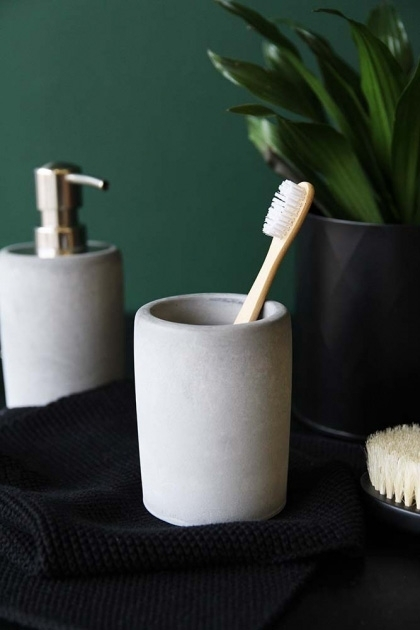 lifestyle image of Concrete Toothbrush Mug with toothbrush in and concrete soap dispenser with plant on black table and dark green wall background