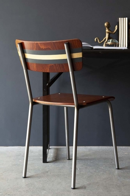 lifestyle image of the back of Contemporary Hand-Painted School Chair - Exclusive Rockett St George Black & Gold with dining table on grey flooring and dark wall background