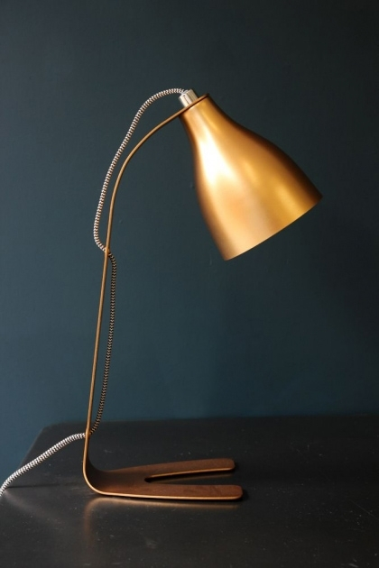 Copper Barefoot Desk Lamp sideways with dark wall background lifestyle image