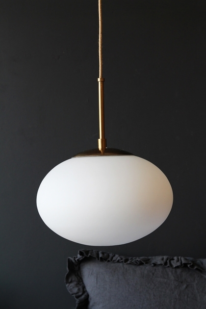 Close-up lifestyle image of the Cruz Opal Pendant Light with dark grey pillow behind and dark wall background