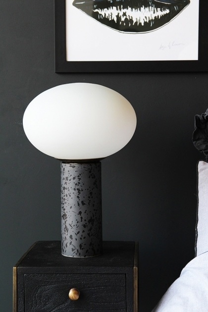 lifestyle image of Cruz Opal Table Lamp on black side table and black and white lips print on dark grey wall background