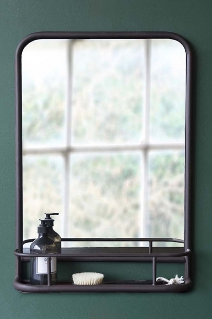 lifestyle image of Dark Brown Mirror With Deep Shelf - Portrait with black soap dispenser in shelf hung on dark green wall background