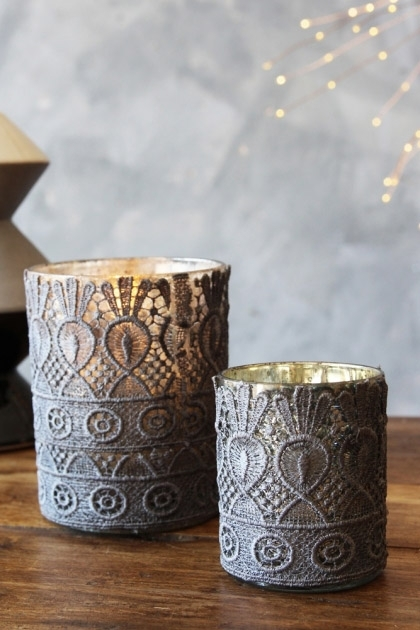 Ilifestyle mage of both sizes of the Davenport Tea Light Holder with lit tea light inside on wooden table with grey wall background