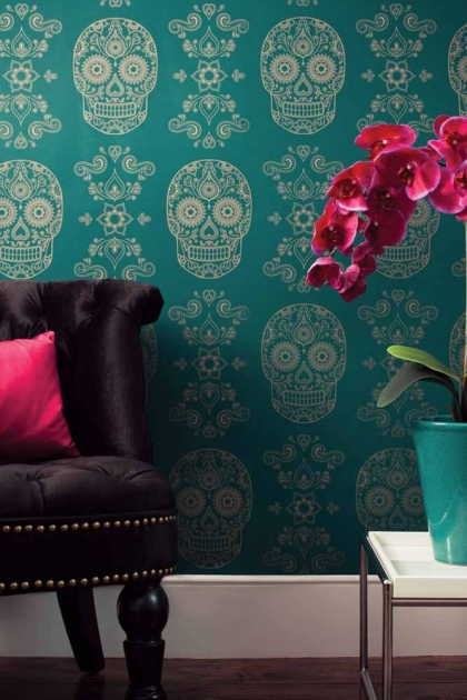 lifestyle image of Day of the Dead Skull Wallpaper - Emerald & Gold with brown chair and pink cushion and white side table with pink flowers in blue vase