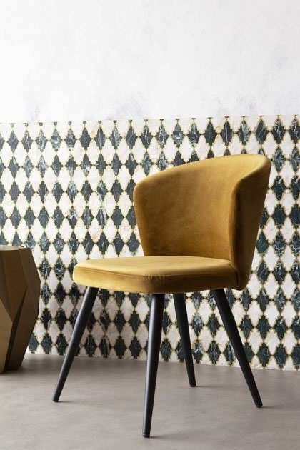 Angled lifestyle image of the Golden Ochre Deco Velvet Dining Chair with patterned wallpaper background with pale grey flooring