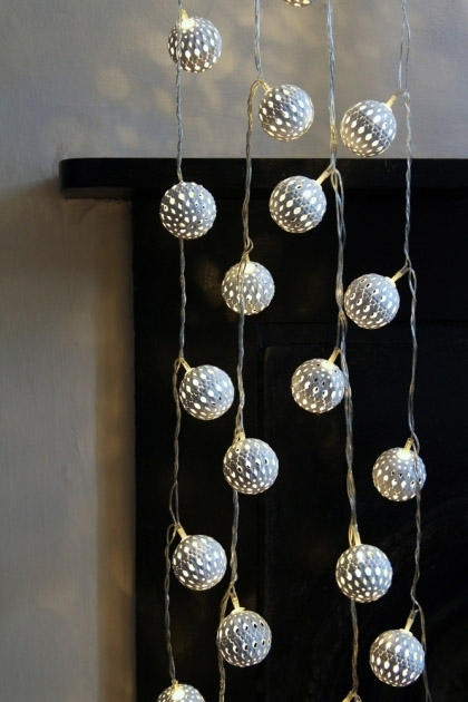 lifestyle image of Decorative White Light Chain - Large Maroq lit up with black fireplace in background