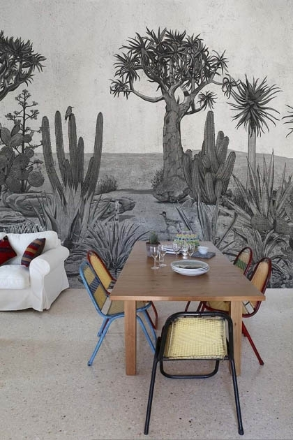 Lifestyle image of the Desert Landscape Wallpaper Mural - Meiji Chai Seed with wooden dining table and colored dining chairs around it with white sofa in background on grey flooring