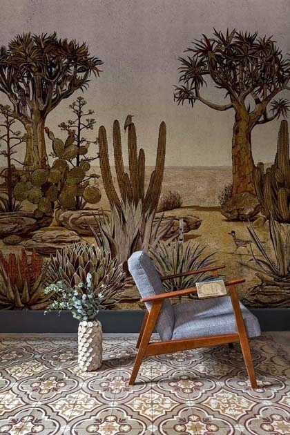 Lifestyle image of the Desert Landscape Wallpaper Mural - Meiji Rose Pink with blue and wooden arm chair and plant in white pot on patterned tile flooring