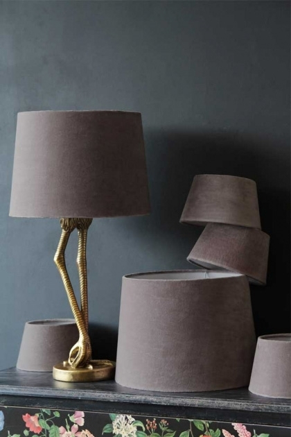 lifestyle image of Dusky Pink Sumptuous Velvet Lamp Shade - Available In 3 Sizes on Antique Gold Flamingo Leg Table Lamp and other shades gathered together on dark background