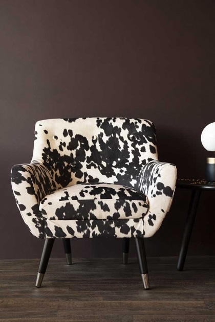 lifestyle image of Faux Cowhide Vintage Style Armchair on wooden floor and dark brown wall background