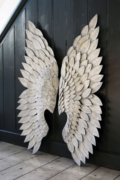 lifestyle image of Feather Effect Metallic Wings leaning on black wood panel wall and on wooden flooring