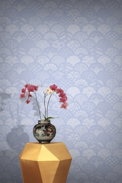lifestyle image of Feathr Silver Feathers Wallpaper - Frost with gold side table and vase with pink flowers