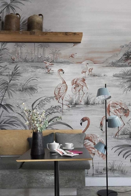 Lifestyle image of the Flamingo Chinoiserie Wallpaper Mural - Chai Seed with breakfast bar and yellow and grey sofa under wooden shelf with brown jugs on and pale blue three headed floor lamp