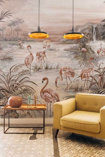 Lifestyle image of the Flamingo Chinoiserie Wallpaper Mural - Rose Pink with yellow armchair with side table with round ornament on top and two ceiling lights hanging from ceiling