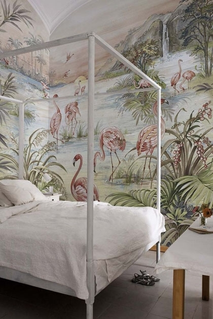Lifestyle image of the Flamingo Chinoiserie Wallpaper Mural - Roseus Maca in bedroom with white four poster bed with white bedding and dark wooden flooring