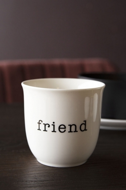 Lifestyle image of the Friend Bone China Mug on black table with other tableware and red velvet dining chair with dark wall background