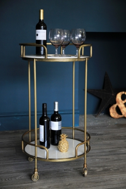 Gatsby Marble & Brass Effect Drinks Trolley with wine glasses bottles dark wall background and wooden flooring lifestyle image
