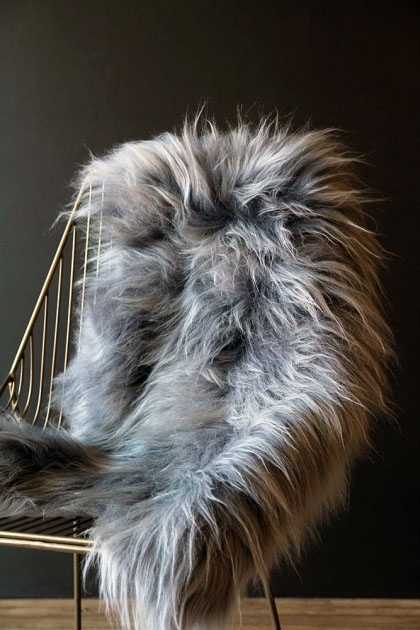 lifestyle image of Genuine Icelandic Long Wool Sheepskin - Silver on midas chair with dark wall background
