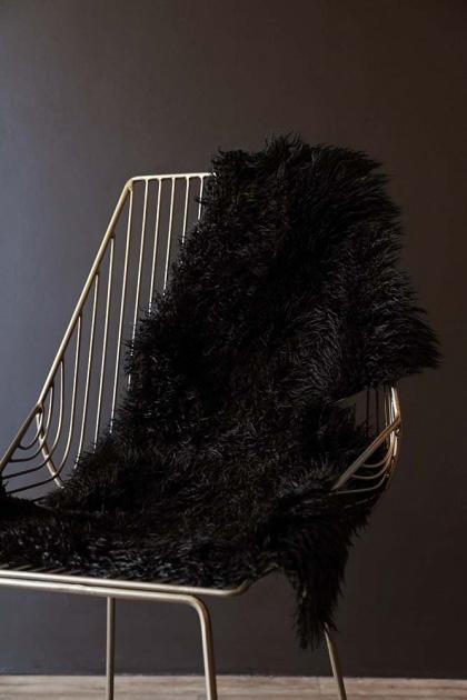 lifestyle image of Genuine New Zealand Long Wool Curly Sheepskin - Black on midas chair on dark wall background