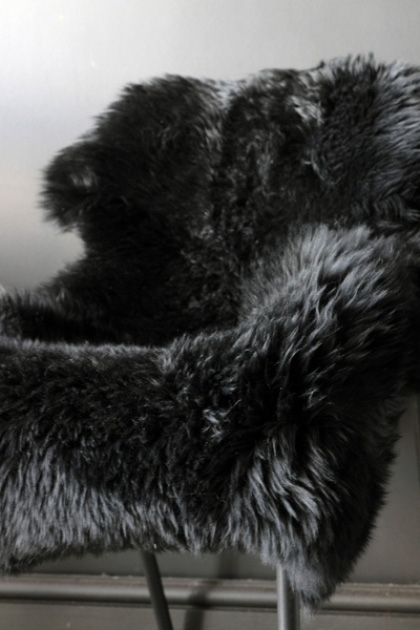 Genuine Sheepskin Rug - Silky Black on chair close up lifestyle image with pale background