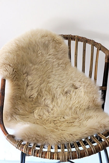 Genuine Sheepskin Rug - Silky Oyster on natural rattan chair with pale background lifestyle image