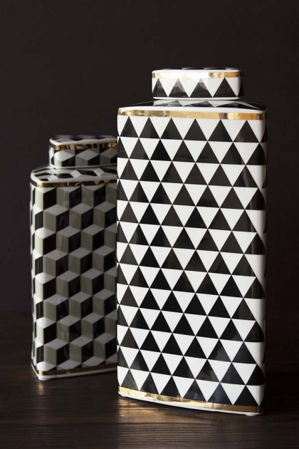 Lifestyle image of the tall Geometric Monochrome Storage Jar with Gold Detail with the Geometric Monochrome Storage Jar with Gold Detail - Short on black side table and dark wall background