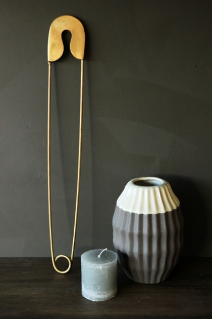 lifestyle image of Giant Brass Coloured Safety Pin standing upright against dark grey wall with grey and white vase and small blue candle