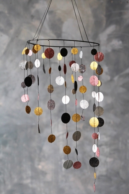 lifestyle image of Glitter Spot Mobile Garland  with distressed grey wall background